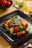 Steak with Vegetables Flambe. Dish on a black plate Royalty Free Stock Photography