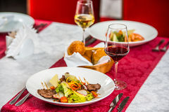 Steak and vegetables on a restaurant table Stock Photos
