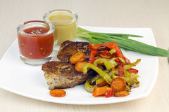 Steak with vegetables and sauces. Stock Images