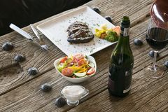 Steak and vegetables on wooden table Stock Photos
