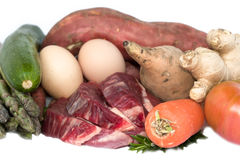 Steak with vegs. Three peaces of uncooked sliced steak beef with two eggs, carrot, ginger, rosemary, red and white sweet potato (batata), zucchini, asparagus Stock Photography