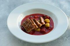 Steak von der Leiste einer Ente mit karamellisierter Erdbeere lizenzfreies stockfoto