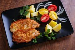 Steak von Schweinefleisch mit Kartoffeln und Tomaten Stockbilder