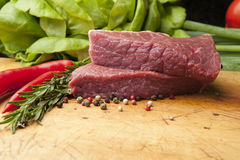 Steak on a wooden board, close up. Wooden cutting board with steak meat, peppercorns and rosemary Stock Photos