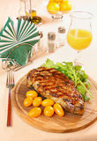 Steak on a wooden plate Royalty Free Stock Images