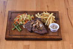 Steak on a wooden plate Royalty Free Stock Photos