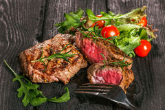 Steak on a wooden table. Steak and salad on a wooden table Stock Photography