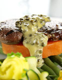 Steak And Yam. Chargrilled steak on sweet potato with green peppercorn sauce Royalty Free Stock Photography