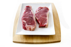 Steaks. Two strip loin steaks on a platter Stock Photos
