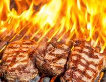 Steaks auf gegrillt mit Flammen stockbild