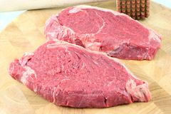 Steaks on a chopping board. Tenderized Steak on a chopping board on a white background Royalty Free Stock Photography