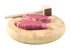 Steaks on a chopping board with Mallet. Tenderized Steak on a chopping board on a white background Royalty Free Stock Photos