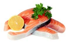 Steaks der roten Fische mit einer Zitrone und einer Petersilie Stockfotografie