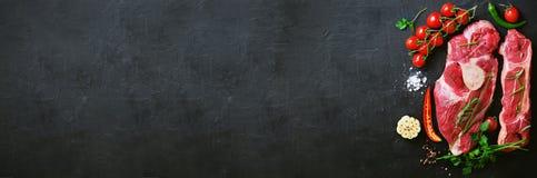 Steaks des rohen Fleisches mit Kirschtomaten, Peperoni, Knoblauch, Öl und Kräutern auf dunklem Stein, konkreter Hintergrund fahne Lizenzfreies Stockfoto