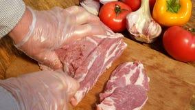 Steaks des rohen Fleisches werden von einem gro?en St?ck Schweinefleisch oder Rindfleisch auf einem h?lzernen Schneidebrett gesch stock video
