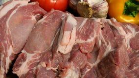 Steaks des rohen Fleisches werden von einem gro?en St?ck Schweinefleisch oder Rindfleisch auf einem h?lzernen Schneidebrett gesch stock video footage