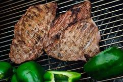 Steaks mit grünen Paprikas auf einem Grill Lizenzfreies Stockfoto