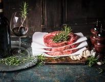 Steaks mit Kräutern und Gewürze und Rotwein auf den gealterten Küchentischen, Vorbereitung kochend Stockbilder