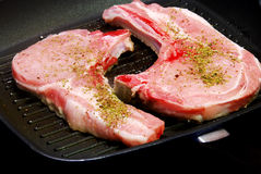 Steaks on pan. Pork steaks cooking on a pan Royalty Free Stock Images