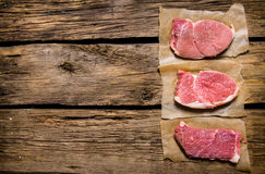 Steaks from raw fresh meat. On wooden background. Royalty Free Stock Photos