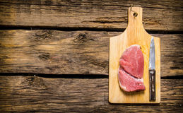 Steaks from raw meat with a butcher knife. Stock Photos