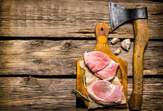 Steaks from raw meat, garlic with an axe. On wooden background. Free space for text . Top view Royalty Free Stock Photography