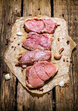 Steaks from raw meat with spices. On wooden background. Steaks from raw meat with spices. On the wooden background Stock Image