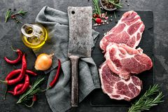 Steaks from Raw pork meat. Fresh steaks from Raw pork meat on dark stone background, Top view stock photos