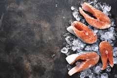 Steaks of raw salmon on ice.Top view with space for text. Steaks of raw salmon on ice on a dark slate,stone or metal background.Top view with space for text Stock Photos