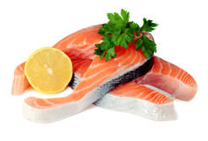 Steaks of red fish with a lemon and parsley. On white background Stock Photography