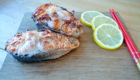 Steaks from red fish with lemon and sauce. Two pieces of fresh red fish with lemon and soy sauce Royalty Free Stock Photography
