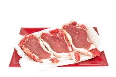 Steaks in red tray isolated Royalty Free Stock Photos