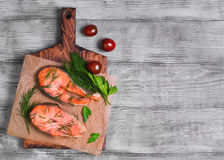 Steaks salmon fish. On cutting board, parsley, dill on paper for fish steaks, light wooden background surface, top view, empty place for text, recipe Stock Photo