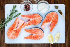 Steaks of salmon with a sprigs of rosemary. Lemon, pepper,  sea salt, , herbs in wooden scoop on a white cutting board on wooden background, top view Stock Photos