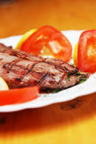 Steaks and tomatoes stock photography