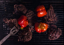 Steaks and vegetables on charcoal bbq grill. With red bell peppers Royalty Free Stock Photography