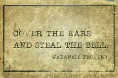 Steal the bell JP. Cover the ears and steal the bell - ancient Japanese proverb printed on grunge vintage cardboard stock photo