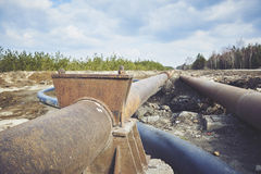 Steal big pipeline on a ground. Old pipes joint. Stock Photos