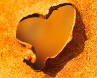 Steal heart. Hole in rusty metal in form heart Stock Image