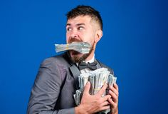 Steal money. Thief with piles dollars money. Earnings surprise concept. Man bearded businessman hold pile money blue. Background. Businessman surprised feels stock images