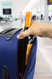 Stealing alcohol at the airport. Stealing wine bottle of a suitcase at the airport Royalty Free Stock Photos