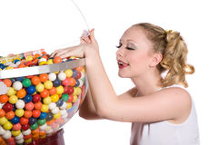 Stealing bubblegum. Pretty blond girl with ponytails reaching into the bubblegum container Royalty Free Stock Image