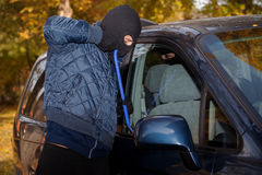 Stealing a car. A masked thief striving to steal a big car Royalty Free Stock Photos