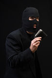Stealing Company Money. Concept image of a thief wearing a black business suit and holding a wallet, shot against a dark background Stock Photos