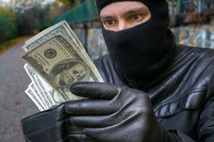 Stealing concept. Masked thief is counting money in stolen walle Stock Photography