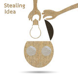 Stealing idea. Hand stealing idea light bulb from head of businessman, burlap Royalty Free Stock Photos