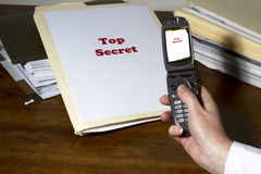 Stealing Industry Secrets. Woman using cell phone app to photograph and steal industry secrets Royalty Free Stock Images