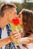 Stealing a kiss behind the lollipop. Royalty Free Stock Images