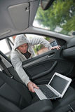 Stealing a laptop. Car theft - a laptop being stolen through the window of an unoccupied car Stock Photo
