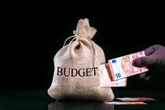 Stealing money from Europe budget. Hand pulls euro out the bag stock image